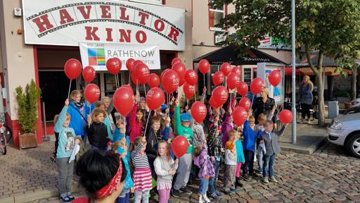 Kinder mit roten Luftballons stehen vor Kino.