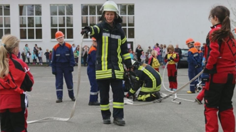 Eine Feuerwehrfrau mit Kindern.