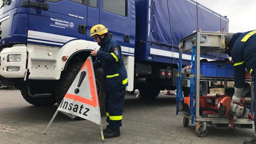Mitarbeiter des THW vor THW-Lastwagen.