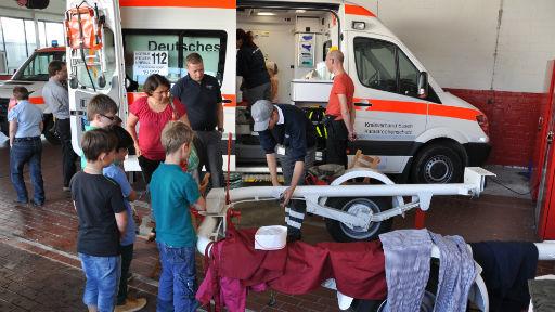 Kinder an Rettungswagen.