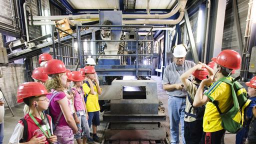 Kinder mit Schutzhelmen in Kraftwerk.