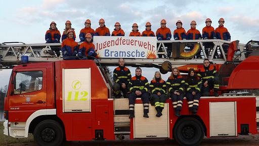 Feuerwehrmannschaft sitzt auf Feuerwehrwagen.