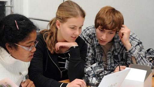Drei Jugendliche hocken vor Computer.