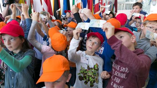Kinder sehen sich 5-Euro Scheine an.
