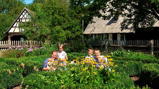 Familie auf Wiese vor altem Bauernhaus.