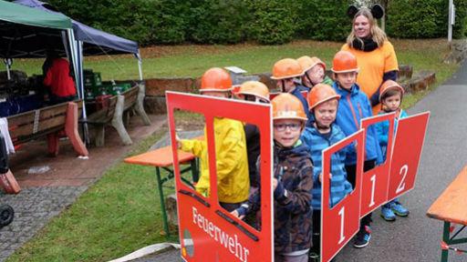 Kinder in kleinem Feuerwehrauto.