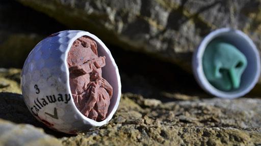 Kunstwerk: Gesicht in halbiertem Golfball.