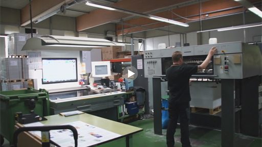 Innenansicht Druckerei, Arbeiter steht an Maschine