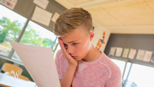 Junge schaut auf ein Blatt und stützt den Kopf in die Hand.; Rechte: WDR