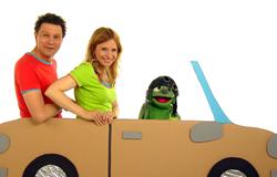 Tanja Mairhofer, André Gatzke und Knolle fahren in der 'Sendung mit dem Elefanten' mit einem Pappauto. (Bildrechte: WDR)