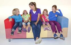 Anke Engelke sitzt für die Sendung 'elefantierisch!' mit vielen Kindern auf einer bunten Couch. (Bildrechte: WDR)