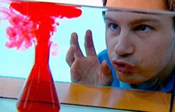 André Gatzke beobachtet eine rote Flüssigkeit, die sich in einem Aquarium ausbreitet.; Rechte: WDR